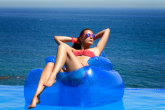 Fashionable Girl Relaxing in the Pool. Summer Vacation. Beautiful young woman sitting on inflatable chair sunbathing. Relax in swimming pool with wonderful sea Stock Photo