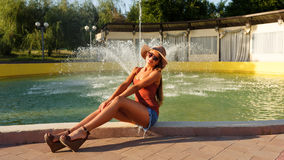 Fashionable girl sits at the fountain Stock Photography