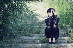 Fashionable girl sits on the stair. Stock Photography