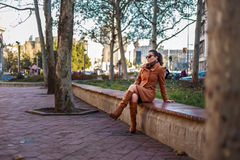 Fashionable girl sitting on a bench. Fashionable girl sitting on a park bench Royalty Free Stock Photos