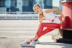 Fashionable girl sitting in red leather pants and white top Royalty Free Stock Images