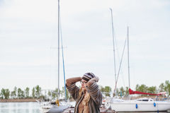Fashionable girl standing in the eyes against white yacht Royalty Free Stock Images