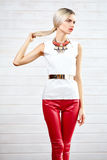 Fashionable girl standing in red leather pants and white top Stock Images