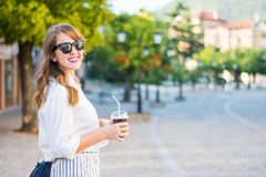 Fashionable girl on the street with coffee to go. Fashionable girl on the street with a coffee to go Royalty Free Stock Image