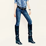 Fashionable girl in stylish jeans clothes and boots on a white b Royalty Free Stock Photo