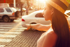 Fashionable girl in the sunny city catches a taxi. Fashionable and beautiful girl walks on the sunny city Stock Photo