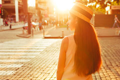 Fashionable girl in the sunny city stands near the road. Fashionable and beautiful girl walks on the sunny city Royalty Free Stock Photo