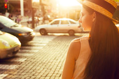 Fashionable girl in the sunny city stands near the road. Fashionable and beautiful girl walks on the sunny city Stock Images