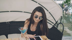 Fashionable girl uses digital tablet resting on beach lounge in 4K.  stock footage