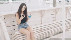 Fashionable girl using phone and goblet of cocktail on the beach bench in 4K stock video