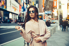 Fashionable girl walking on New York City street in Midtown wearing sunglasses and ping jacket. stock images