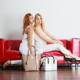 Fashionable girls with bags handbags on red couch Royalty Free Stock Images