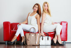 Fashionable girls with bags handbags on red couch. Elegant outfit. Female fashion. Two women blonde and mixed race wearing fashionable clothes high heels with Royalty Free Stock Images