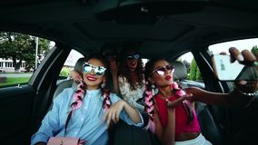 Fashionable girls having fun together inside car and taking photo on smart phone.