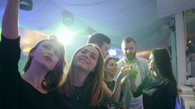 Fashionable girls at nightclub makes selfie photo on mobile phone on background of disco lights behind bar counter stock video