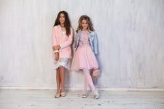 Fashionable girls school girlfriends in white pink dresses