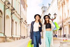Fashionable girls walking with shopping bags Royalty Free Stock Photo