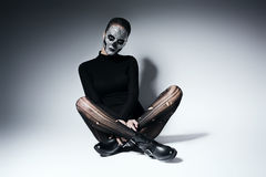 Fashionable gothic woman sitting on the floor. In studio Stock Photo