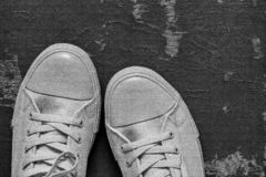 Gray gym shoes closeup on an old shabby background. Fashionable gray sports shoes or gym shoes closeup and separately on an old dirty shabby black background stock photography