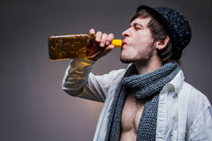 Fashionable guy in a hat drink some tequila. Fashionable guy in a hat drinking tequila Stock Photography