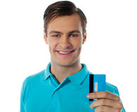 Fashionable guy holding debit card. Fashionable young guy posing with debit card against white background Stock Photography