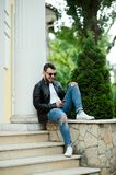 Fashionable guy wearing black leather jacket, sunglasses, tshirt and trousers holding cell phone typing messages to his friend stock photo
