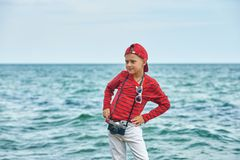 Fashionable handsome boy on the sea coast . Rest and travel . Child posing with an old camera royalty free stock photography