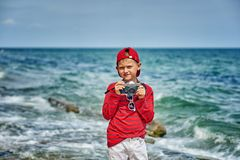 Fashionable handsome boy on the sea coast . Rest and travel . Child posing with an old camera stock photography