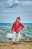 Fashionable handsome boy on the sea coast . Rest and travel . Child posing with an old camera royalty free stock photos