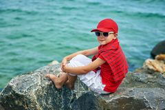 Fashionable handsome boy on the sea coast . Rest and travel . The child sits on a stone in light trousers stock images