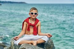 Fashionable handsome boy on the sea coast . Rest and travel . The child sits on a stone in light trousers royalty free stock image