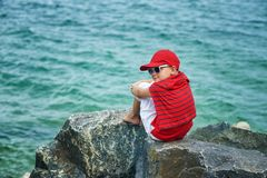 Fashionable handsome boy on the sea coast . Rest and travel . The child sits on a stone in light trousers stock photography