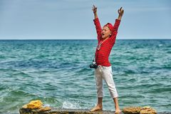 Fashionable handsome boy on the sea coast . Rest and travel . Child posing with an old camera royalty free stock photo