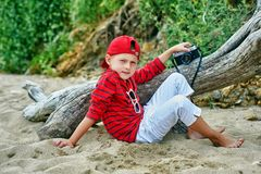 Fashionable handsome boy on a summer walk . Rest and travel . Child posing with an old camera stock image