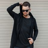 Fashionable handsome man in a black hoody with sunglasses. Posing near a metal wall stock photo