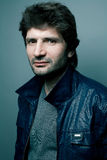 Fashionable handsome man in blue leather jacket Royalty Free Stock Photography