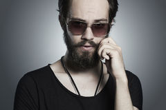 Fashionable handsome man. Brutal bearded boy in trendy sunglasses Royalty Free Stock Image