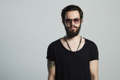 Fashionable handsome man. Brutal bearded boy in trendy glasses stock photography
