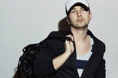Fashionable Handsome Man with handbag. Stylish Boy in cap Stock Photography