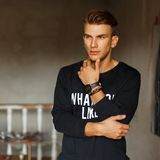 Fashionable handsome stylish man in a pullover with the text. Stands in the art studio. Artist royalty free stock photos