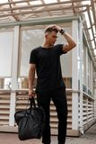 Fashionable handsome young stylish man with hairstyle. In black clothes with a black bag near a wooden building royalty free stock photo