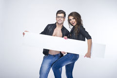 Fashionable happy couple holding white board Royalty Free Stock Image