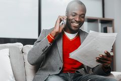 Fashionable happy guy reading notes and communicating. Waist up portrait of stylish african man relaxing on sofa. He is looking at records with smile and talking Stock Photography
