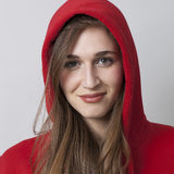 Fashionable happy 20s girl wearing a hoodie on for coolness. Closeup portrait of beautiful smiling 20s woman wearing red hoodie with long hair for cool attitude stock photos