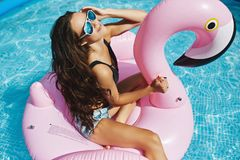 Fashionable, happy and smiling brunette model girl with perfect body in stylish black bikini and glamorous. Sunglasses, posing on an inflatable pink flamingo at stock image