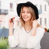 Fashionable happy young hipster woman in a knitted stylish sweater in fashionable sunglasses in an elegant black hat sitting royalty free stock photo