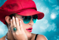 Fashionable Hip Hop Girl. Beauty Brunette with Red Hat. Portrait of fashionable hip hop girl with red cap, blue glasses and beautiful manicure Royalty Free Stock Photo