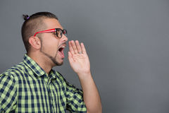 Fashionable hipster man screaming in studio. Close-up profile of fashionable hipster man shouting to someone in photo studio. Young freelancer dreaming about his Royalty Free Stock Images