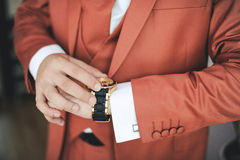 Fashionable jacket. Expensive gold watch on a hand of the groom Royalty Free Stock Images