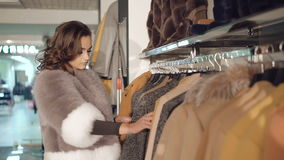 Fashionable lady choosing the fur coats in boutique stock footage